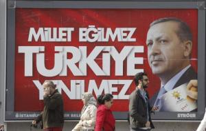 People walk past a poster for Erdogan's election campaign in Istanbul